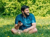 Hombre joven que se sienta en el parque y el mensaje que manda un SMS Imagen de archivo