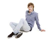 Hombre joven que se sienta en el piso Fotografía de archivo libre de regalías