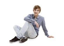 Hombre joven que se sienta en el piso Imágenes de archivo libres de regalías