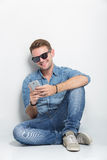Hombre joven que se sienta en el piso mientras que hace algo con su SM Imagenes de archivo