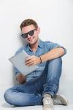 Hombre joven que se sienta en el piso que sostiene una PC de la tableta Fotos de archivo libres de regalías
