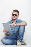 Hombre joven que se sienta en el piso que sostiene una PC de la tableta Fotos de archivo