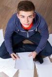Hombre joven que se sienta en el piso y el aprendizaje Imagenes de archivo