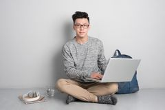 Hombre joven que se sienta en el piso y que usa el ordenador portátil fotos de archivo libres de regalías