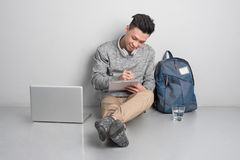 Hombre joven que se sienta en el piso y que usa el ordenador portátil imagenes de archivo