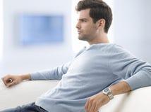 Hombre joven que se sienta en el sofá fotografía de archivo libre de regalías
