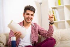 Hombre joven que se sienta en el sofá Imagen de archivo