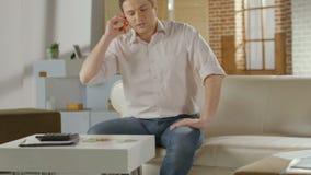 Hombre joven que se sienta en el sofá en casa, teniendo conversación telefónica metrajes