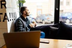 Hombre joven que se sienta en el sofá en un café, un café de consumición y mirando la ventana a la calle de la ciudad Fotografía de archivo
