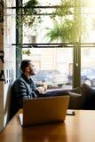 Hombre joven que se sienta en el sofá en un café, un café de consumición y mirando la ventana a la calle de la ciudad Fotos de archivo