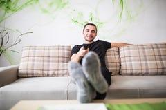 Hombre joven que se sienta en el sofá usando un teledirigido en casa Fotos de archivo libres de regalías