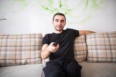 Hombre joven que se sienta en el sofá usando un teledirigido en casa Imagen de archivo libre de regalías