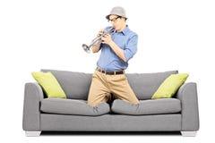 Hombre joven que se sienta en el sofá y que sopla en la trompeta Fotografía de archivo libre de regalías