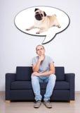 Hombre joven que se sienta en el sofá y que sueña sobre perro sobre la pared blanca Foto de archivo