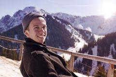 Hombre joven que se sienta en el sol rodeado por las montañas nevosas Imagenes de archivo
