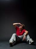 Hombre joven que se sienta en el suelo Fotografía de archivo