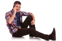 Hombre joven que se sienta en el teléfono Fotografía de archivo libre de regalías