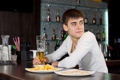 Hombre joven que se sienta en esperar contrario de la barra Fotografía de archivo libre de regalías