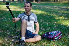 Hombre joven que se sienta en hierba y que toma el selfie en una cámara de la acción Imagenes de archivo