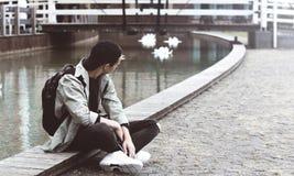 Hombre joven que se sienta en la acera cerca del lago Fotografía de archivo