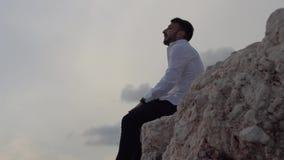 Hombre joven que se sienta en la alta colina de la roca y que disfruta de la vista asombrosa de la playa Individuo feliz que grit almacen de video