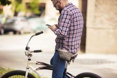 Hombre joven que se sienta en la bici usando móvil Imagen de archivo libre de regalías