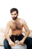 Hombre joven que se sienta en la cama Fotografía de archivo libre de regalías