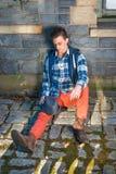 Hombre joven que se sienta en la esquina Fotografía de archivo