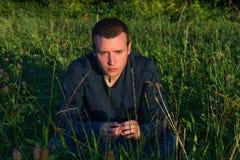 Hombre joven que se sienta en la hierba foto de archivo