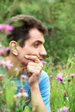 Hombre joven que se sienta en la hierba Fotografía de archivo libre de regalías