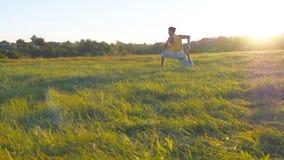 Hombre joven que se sienta en la hierba verde en el prado y que hace ejercicio de la yoga Individuo muscular que estira su cuerpo fotos de archivo libres de regalías