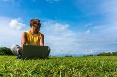 Hombre joven que se sienta en la hierba y que trabaja con el ordenador portátil Fotografía de archivo
