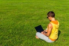 Hombre joven que se sienta en la hierba y que trabaja con el ordenador portátil Imagen de archivo libre de regalías