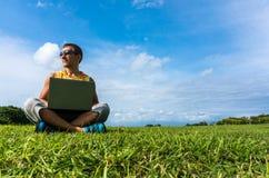 Hombre joven que se sienta en la hierba y que trabaja con el ordenador portátil Imagenes de archivo