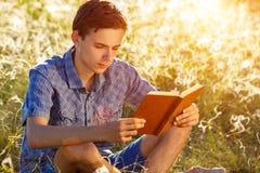 Hombre joven que se sienta en la naturaleza que lee un libro fotos de archivo