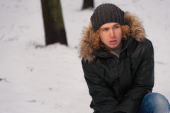 Hombre joven que se sienta en la nieve en el parque del invierno Imagen de archivo