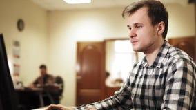 Hombre joven que se sienta en la oficina, trabajando en un ordenador y hablar metrajes