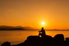 Hombre joven que se sienta en la pesca de piedra en la puesta del sol del mar Imagen de archivo libre de regalías