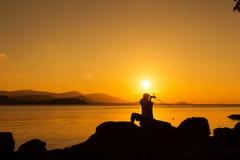 Hombre joven que se sienta en la pesca de piedra en la puesta del sol del mar Fotografía de archivo libre de regalías