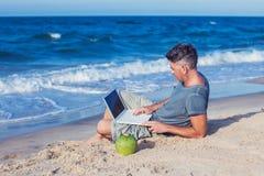 Hombre joven que se sienta en la playa con la computadora portátil fotografía de archivo libre de regalías