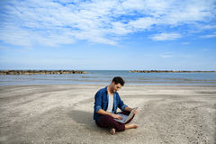 Hombre joven que se sienta en la playa con la computadora portátil foto de archivo