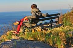 Hombre joven que se sienta en la playa en la salida del sol Foto de archivo libre de regalías