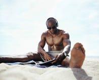 Hombre joven que se sienta en la playa que lee una revista Imagenes de archivo