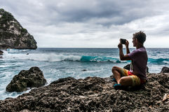 Hombre joven que se sienta en la roca y que hace una foto de las ondas Fotografía de archivo libre de regalías