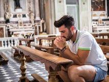 Hombre joven que se sienta en la rogaci?n de la iglesia fotos de archivo