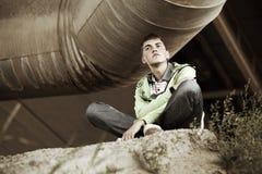 Hombre joven que se sienta en la tierra Fotos de archivo libres de regalías