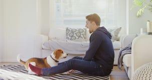 Hombre joven que se sienta en la tierra que juega con su perro casero 4K 4k metrajes