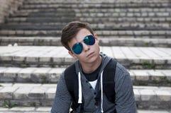 Hombre joven que se sienta en las escaleras en la calle de la ciudad Fotos de archivo libres de regalías
