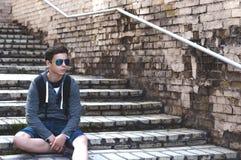 Hombre joven que se sienta en las escaleras en la calle de la ciudad Fotos de archivo