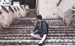 Hombre joven que se sienta en las escaleras en la calle de la ciudad Fotografía de archivo